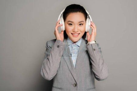 Photo pour Jeune femme d'affaires souriante dans un casque sur fond gris - image libre de droit