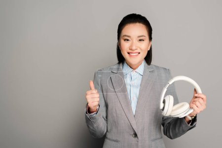 Photo pour Smiling young businesswoman holding headphones and showing thumb up on grey background - image libre de droit
