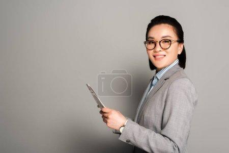 Foto de Vista lateral de la joven mujer de negocios sonriente en gafas con periódico sobre fondo gris - Imagen libre de derechos