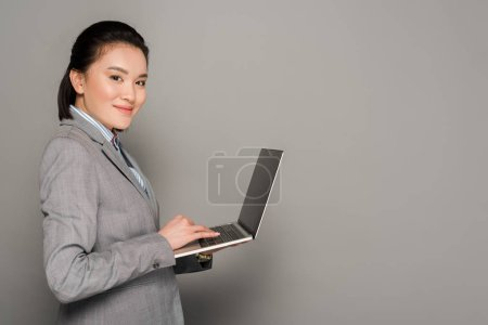 Photo for Side view of smiling young businesswoman in suit using laptop on grey background - Royalty Free Image
