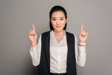 smiling young businesswoman pointing with fingers up on grey background