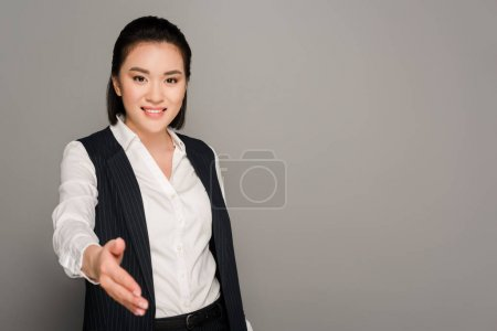 Photo for Smiling young businesswoman giving hand on grey background - Royalty Free Image