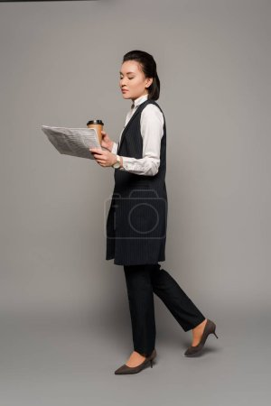Photo for Young businesswoman reading newspaper and drinking coffee on grey background - Royalty Free Image