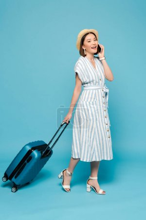 Photo for Smiling brunette asian girl in striped dress and straw hat with travel bag talking on smartphone on blue background - Royalty Free Image