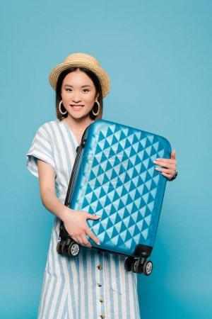 Photo pour Sourire brunette asiatique fille en robe rayée et chapeau de paille avec sac de voyage sur fond bleu - image libre de droit