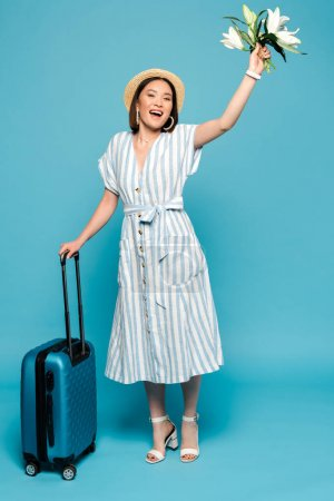 Photo pour Heureux brunette asiatique fille en robe rayée et chapeau de paille avec sac de voyage et bouquet de lis sur fond bleu - image libre de droit