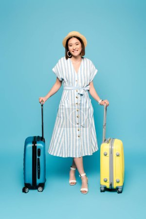 Photo pour Sourire brunette asiatique fille en robe rayée et chapeau de paille avec des sacs de voyage sur fond bleu - image libre de droit