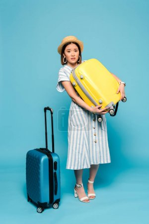 Photo pour Triste brunette asiatique fille en robe rayée et chapeau de paille avec des sacs de voyage sur fond bleu - image libre de droit