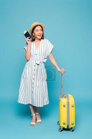 Photo pour Sourire brunette asiatique fille en robe rayée et chapeau de paille avec sac de voyage et passeport avec billet d'avion sur fond bleu - image libre de droit
