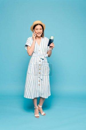 Photo pour Sourire brunette asiatique fille en robe rayée et chapeau de paille avec passeport et billet d'avion parler sur smartphone sur fond bleu - image libre de droit