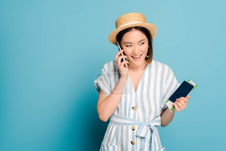 Photo for Smiling brunette asian girl in striped dress and straw hat holding passport with boarding pass while talking on smartphone on blue background - Royalty Free Image