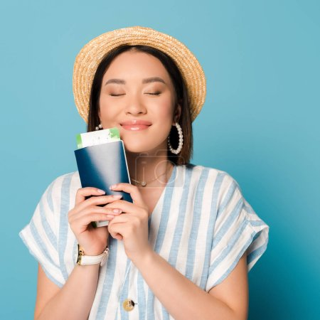Photo pour Pleased brunette asian girl in striped dress and straw hat holding passport with boarding pass on blue background - image libre de droit