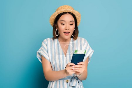 Photo pour Excited brunette asian girl in striped dress and straw hat holding passport with boarding pass on blue background - image libre de droit