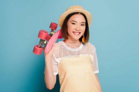 Foto de Sonriente chica asiática vestida de amarillo rayado y sombrero de paja con tablero de pluma rosa sobre fondo azul. - Imagen libre de derechos