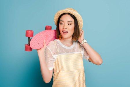 Foto de Chica asiática con vestido de color amarillo rayado y sombrero de paja con tablero de pluma rosa en fondo azul. - Imagen libre de derechos