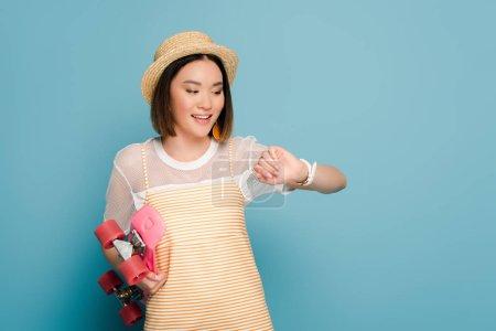Foto de Sonriente chica asiática vestida de amarillo rayado y sombrero de paja con tablero de pluma rosa mirando al reloj de pulsera en fondo azul. - Imagen libre de derechos