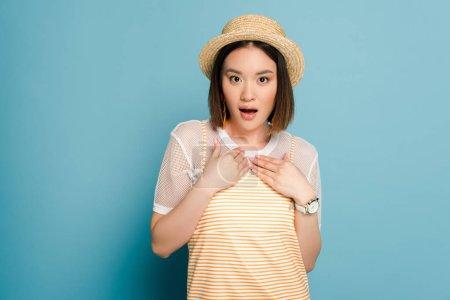 Foto de Shock asian girl with striped yellow dress and straw hat on blue background. - Imagen libre de derechos