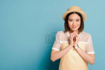 Foto de Jovencita asiática con vestido de color amarillo rayado y sombrero de paja en fondo azul. - Imagen libre de derechos