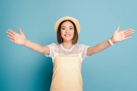 sonriente chica asiática en rayas vestido amarillo y sombrero de paja con los brazos abiertos sobre fondo azul