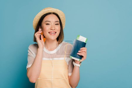 Photo pour Smiling asian girl in striped yellow dress and straw hat holding passport with boarding pass and talking on smartphone on blue background - image libre de droit