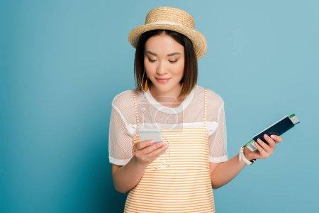 Foto de Sonriente chica asiática vestida de amarillo rayado y sombrero de paja que tiene pasaporte con tarjeta de embarque y teléfono inteligente en fondo azul. - Imagen libre de derechos