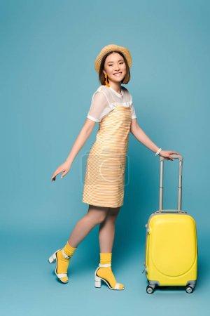 Photo pour Sourire asiatique fille en robe jaune rayé et chapeau de paille avec valise sur fond bleu - image libre de droit