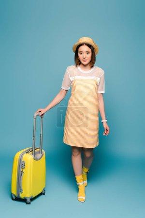 Foto de Chica asiática con vestido de color amarillo rayado y sombrero de paja con maleta en fondo azul. - Imagen libre de derechos