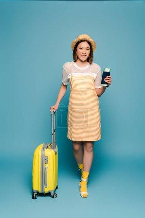 Photo pour Sourire asiatique fille en robe jaune rayé et chapeau de paille tenant passeport et valise sur fond bleu - image libre de droit