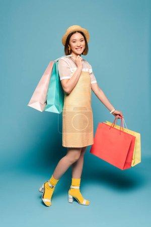 Foto de Sonriente chica asiática vestida de amarillo rayado y sombrero de paja con bolsas de compras en fondo azul. - Imagen libre de derechos