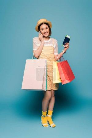 Photo pour Sourire asiatique fille en robe jaune rayé et chapeau de paille avec des sacs à provisions et passeport parler sur smartphone sur fond bleu - image libre de droit