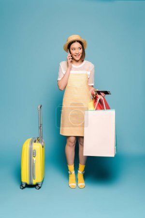 Photo pour Sourire asiatique fille en robe jaune rayé et chapeau de paille avec des sacs à provisions, passeport et valise parler sur smartphone sur fond bleu - image libre de droit