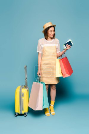 smiling asian girl in striped yellow dress and straw hat with shopping bags, passport and suitcase on blue background