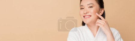 Photo for Smiling beautiful asian woman in bathrobe touching face isolated on beige, panoramic shot - Royalty Free Image