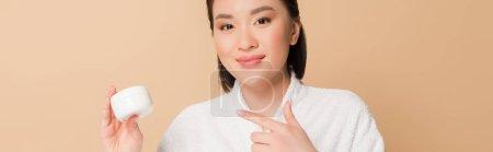 Photo pour Sourire belle asiatique femme en peignoir pointant avec doigt à la crème cosmétique isolé sur beige, panoramique shot - image libre de droit