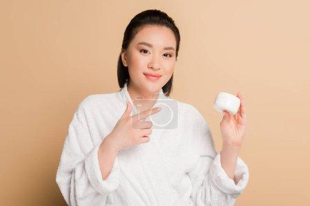 Photo pour Sourire belle asiatique femme en peignoir pointant avec doigt à la crème cosmétique sur fond beige - image libre de droit