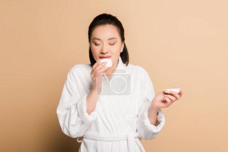Photo pour Sourire belle asiatique femme en peignoir sentant crème cosmétique sur fond beige - image libre de droit