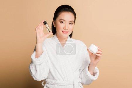 Photo pour Belle femme asiatique souriante en peignoir tenant crème cosmétique et huile sur fond beige - image libre de droit