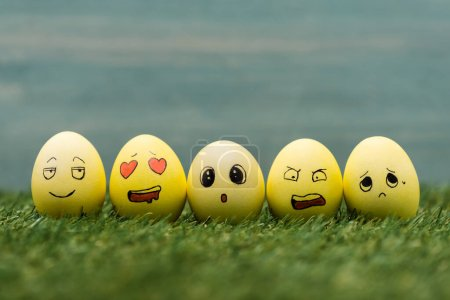 Easter eggs with different facial expressions on grass