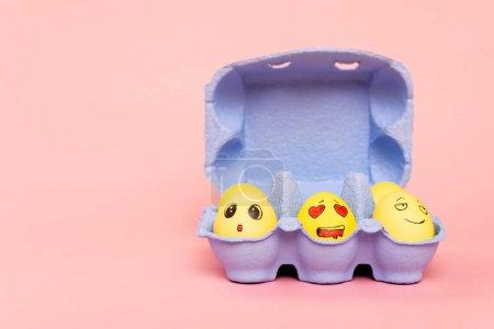 Photo pour Œufs de poulet peints avec expressions faciales dans un bac à œufs violet sur fond rose, concept Pâques - image libre de droit