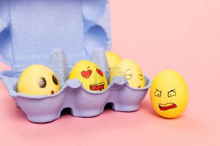 Photo pour Oeufs de poulet drôles avec expressions faciales dans un bac à œufs rose, concept de Pâques - image libre de droit