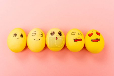 Photo for Top view of painted Easter eggs with different facial expressions on pink background - Royalty Free Image