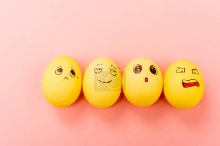 Top view of Easter eggs with different funny facial expressions on pink background