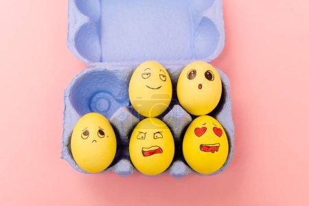 Draufsicht auf bunte Ostereier mit Gesichtsausdruck in Eierschale auf rosa Hintergrund