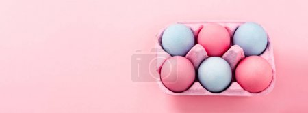 Photo for High angle view of colorful easter eggs in egg tray on pink background, panoramic shot - Royalty Free Image
