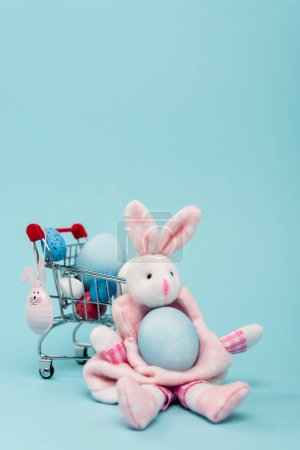 Photo for Cart with colorful easter eggs and decorative bunnies on blue background - Royalty Free Image