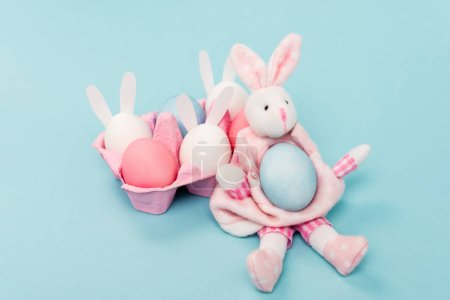 Foto de Pink egg tray with painted chicken eggs and decorative bunnies on blue, easter concept - Imagen libre de derechos