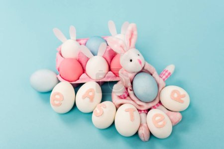 Foto de Painted chicken eggs with easter lettering and decorative bunnies on blue background - Imagen libre de derechos