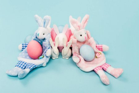 Foto de Painted chicken eggs and decorative easter bunnies on blue background - Imagen libre de derechos