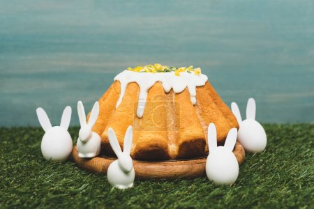 Foto de Easter cake on wooden board and decorative bunnies on grass - Imagen libre de derechos