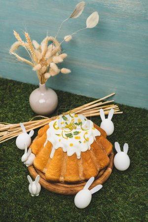 Foto de High angle view of Easter cake with decorative bunnies and vase with willow and wheat on grass - Imagen libre de derechos